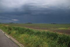 Den mörka åskvädret fördunklar ovanför polder Wilde Veenen i Waddinxveen i Nederländerna arkivbild