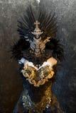 Den mörka gotiska klänningen bildade vid en silvermetalltiara och guld- Co Royaltyfria Foton