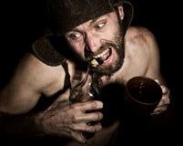 Den mörka ståenden av den läskiga onda illavarslande skäggiga mannen med flin, öppnar han en flaska av konjak hans tänder konstig Arkivbild