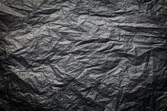 Den mörka texturen av skrynkligt papper, svart bakgrund Arkivbild