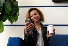 Den mörkhyade flickan med ett exponeringsglas av kaffe är le och se en mobiltelefon V?ntande rum p? flygplats- eller drevstatione royaltyfria foton