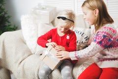 Den magiska gåvaasken och ett barn behandla som ett barn flickor, julmirakel, den lilla härliga lyckliga le flickan öppnar en ask royaltyfri foto