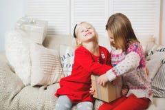 Den magiska gåvaasken och ett barn behandla som ett barn flickor, julmirakel, den lilla härliga lyckliga le flickan öppnar en ask arkivbilder