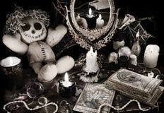 Den magiska ritualen med voodoodockan, spegeln och tarokkort i tappninggrunge utformar Fotografering för Bildbyråer