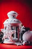 Den magiska vita lyktan står med den vita rät maskastjärnan på den och en granträdfilial och en kasta snöboll på en röd bakgrund  Arkivfoto