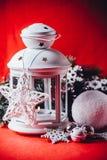 Den magiska vita lyktan står med den vita rät maskastjärnan på den och en granträdfilial och en kasta snöboll på en röd bakgrund  Royaltyfri Fotografi