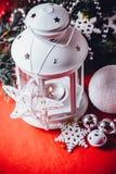 Den magiska vita lyktan står med den vita rät maskastjärnan på den och en granträdfilial och en kasta snöboll på en röd bakgrund  Arkivbild