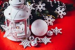 Den magiska vita lyktan står med den vita rät maskastjärnan på den och en granträdfilial och en kasta snöboll på en röd bakgrund  Royaltyfria Foton