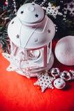 Den magiska vita lyktan står med den vita rät maskastjärnan på den och en granträdfilial och en kasta snöboll på en röd bakgrund  Royaltyfria Bilder