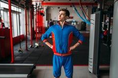 Den magra mannen i sportswear visar hans muskler, idrottshall royaltyfri fotografi