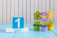 Den Maj 1st bilden av kan 1 träfärgkalender på vit bakgrund med blommor Vårdagen, tömmer utrymme för text Arkivbilder