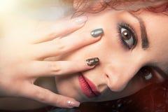 Den makeupframsidan och handen spikar den unga kvinnan gör teen övre arkivfoton