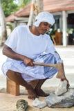 Den maldiviska byggnadsarbetaren i traditionell nationell maldivian kläder som knäcker korall, vaggar med yxan royaltyfria bilder