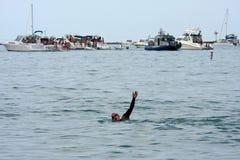 Den Male simmaren gör ryggsim Amid att festa för fartyg royaltyfri bild