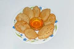 Den Malpua- tjänade som den indiska traditionella efterrätten eller pannkakan för festivaler, i platta med Jaggerysirap royaltyfri bild