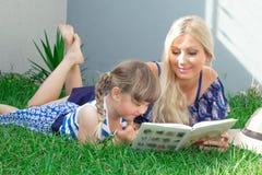 Den mammablondinen och dottern ligger på gräset och läsningen en bok, lycklig familj fotografering för bildbyråer