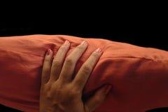Den Manicured kvinnliga handen med apelsinen spikar polermedel som griper den orange kudden royaltyfri bild