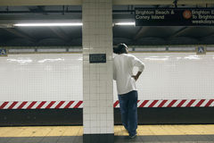 Den manliga afrikanska amerikanen väntar på plattformen av gångtunnelstationen Arkivfoton