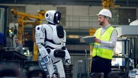 Den manliga arbetaren ger anvisningar till en cyborg arkivfilmer