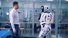 Den manliga arbetaren kontrollerar jämvikt för robot` s, medan skjuta den 4K arkivfilmer