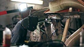 Den manliga arbetaren på en svetsningfabrik i en svetsningmaskering arbetar med metallkonstruktion Svetsning på en industrianlägg lager videofilmer