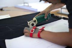 Den manliga arbetaren på en sy tillverkning använder den elektriska bitande tygmaskinen med kedjehandsken arkivfoto