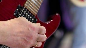 Den manliga assistenten spelar med en hacka på den elektriska gitarren N?rbild f?r gitarrillustration f?r begrepp elektrisk musik stock video