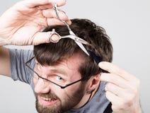 Den manliga barberaren klipper hans egen mustasch som ser kameran som spegeln den stilfulla yrkesmässiga frisören uttrycker Arkivfoton
