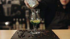 Den manliga baristahanden gör mojito, genom att tillfoga sockerpulver in i ett exponeringsglas med grön sirap, limefrukt och mint stock video