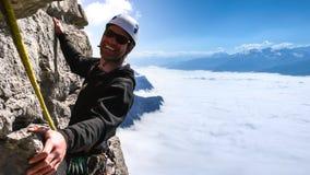 Den manliga berghandboken som ler på en brant lodlinje, vaggar klättring i ursnygg omgivning högt ovanför ett hav av moln i dalen royaltyfri foto