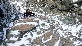 Den manliga bergsbestigaren i ett brant vaggar och iscouloir på hans väg till en hög alpin toppmöte royaltyfri foto