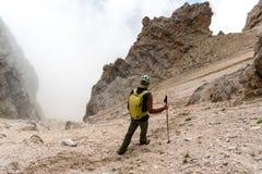 Den manliga bergsbestigaren på en brant stenras och vaggar nedstigning i dolomitesna av Italien i Alta Badia royaltyfri bild