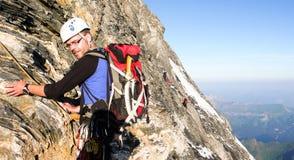 Den manliga bergsbestigaren på ett brant vaggar framsidan på hans väg till det berömda Eiger berget i de schweiziska fjällängarna royaltyfri fotografi