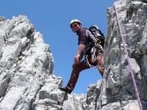 Den manliga bergsbestigaren på ett brant vaggar klättringrutten i de schweiziska fjällängarna nära Klosters arkivbild