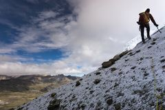 Den manliga bergsbestigaren på ett brant vaggar och snöar lutningen i Anderna royaltyfri foto