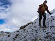 Den manliga bergsbestigaren på ett brant vaggar och snöar lutningen i Anderna royaltyfria foton