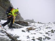 Den manliga bergsbestigaren som heading upp en brant snö och, vaggar lutningen i dåligt väder i de höga fjällängarna av Schweiz arkivfoto
