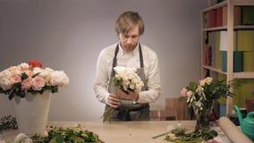 Den manliga blomsterhandlaren räcker closeupen, snitt steg för bukett i blomsterhandel Man assistenten eller ägaren i studion för stock video