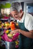 Den manliga blomsterhandlaren som bevattnar blommor med att bevattna kan Royaltyfri Fotografi