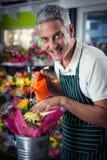 Den manliga blomsterhandlaren som bevattnar blommor med att bevattna kan Arkivfoton