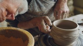 Den manliga ceramisten koncentreras på danandekrukan från lera på snurr som kastar hjulet Han korrigerar formen av lergods lager videofilmer