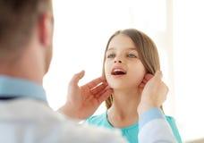 Den manliga doktorn kontrollerar liten flickalymfaknutpunkter Royaltyfri Bild