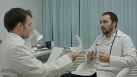 Den manliga doktorn och barnet internerar godlynt samtal om nya medicinska researchs Royaltyfri Bild