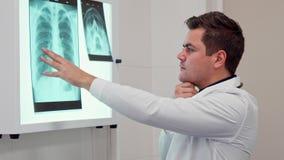 Den manliga doktorn rymmer hans hand på röntgenstrålebilden royaltyfri foto