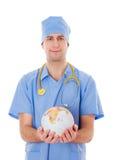 Den manliga doktorn rymmer världsjordklotet i hans händer. royaltyfria bilder