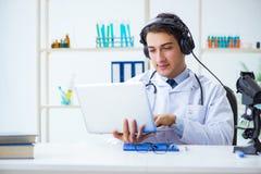 Den manliga doktorn som lyssnar till patienten under telemedicineperiod arkivfoto
