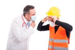 Den manliga doktorn som ser konstruktörhuvudet, smärtar skada royaltyfri foto
