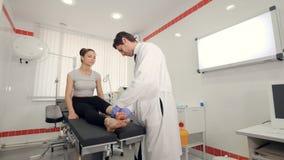 Den manliga doktorn undersöker patienter lägger benen på ryggen, det medicinska tidsbeställningsbegreppet 4K arkivfilmer