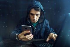 Den manliga en hacker använder mobiltelefonen för att hacka systemet begrepp av brottet och att hacka för cyber elektroniska appa royaltyfri fotografi