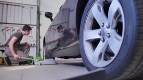 Den manliga förlagen lyfter hjulet av en bil med en stålar för att reparera den i en bilreparation shoppar Hjälpmedel bucklajuste lager videofilmer